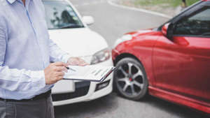 a person standing next to a car: Car Insurance Deductible