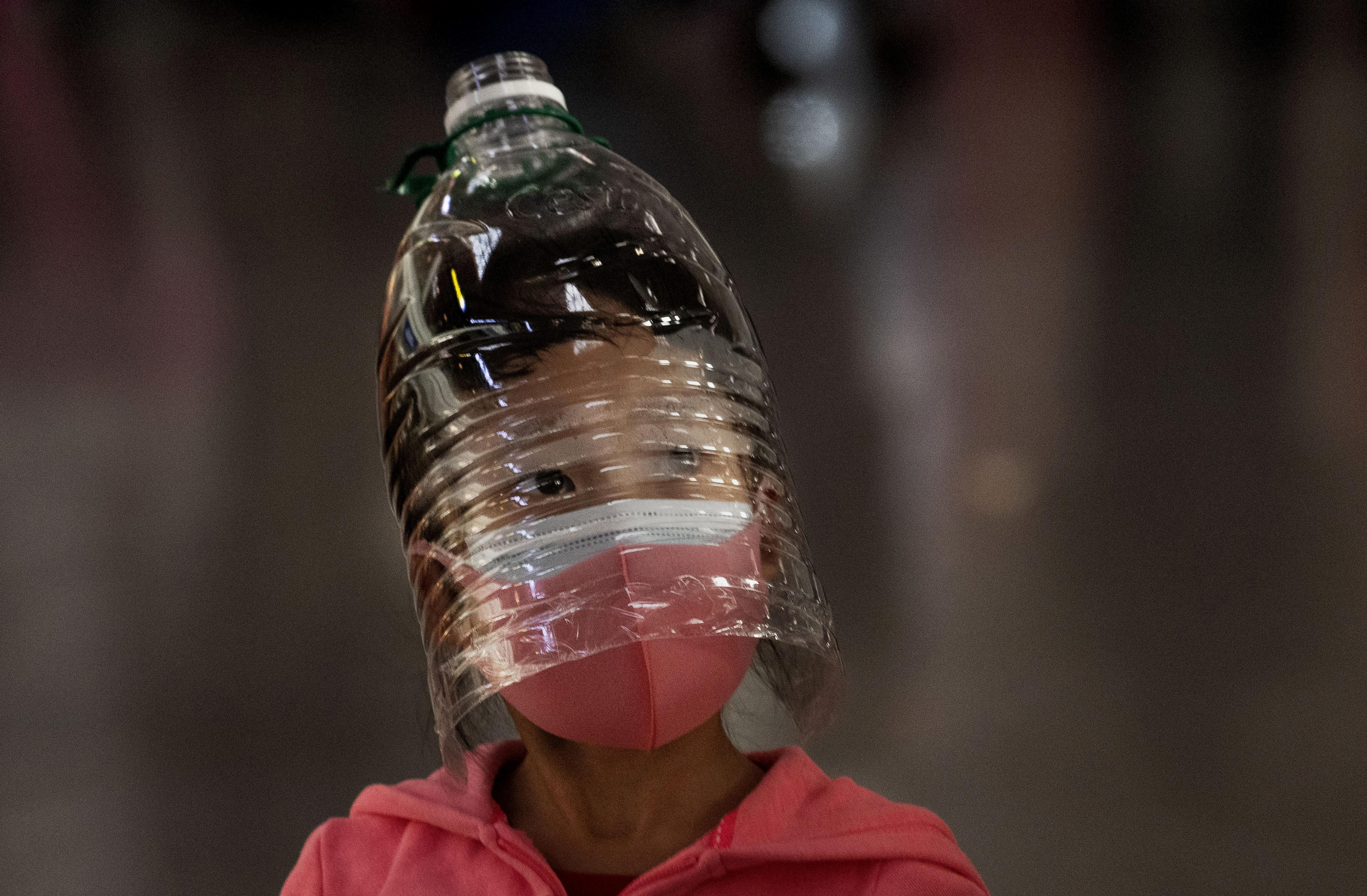 Slide 109 of 113: A Chinese girl wears a plastic bottle as makeshift homemade protection and a protective mask while waiting to check in to a flight at Beijing Capital Airport on Jan. 30, 2020 in Beijing, China. The number of cases of a deadly new coronavirus rose to over 7000 in mainland China Thursday as the country continued to lock down the city of Wuhan in an effort to contain the spread of the pneumonia-like disease which medicals experts have confirmed can be passed from human to human. In an unprecedented move, Chinese authorities put travel restrictions on the city which is the epicenter of the virus and neighboring municipalities affecting tens of millions of people. The number of those who have died from the virus in China climbed to over 170 on Thursday, mostly in Hubei province, and cases have been reported in other countries including the United States, Canada, Australia, Japan, South Korea, and France. The World Health Organization has warned all governments to be on alert, and its emergency committee is to meet later on Thursday to decide whether to declare a global health emergency.