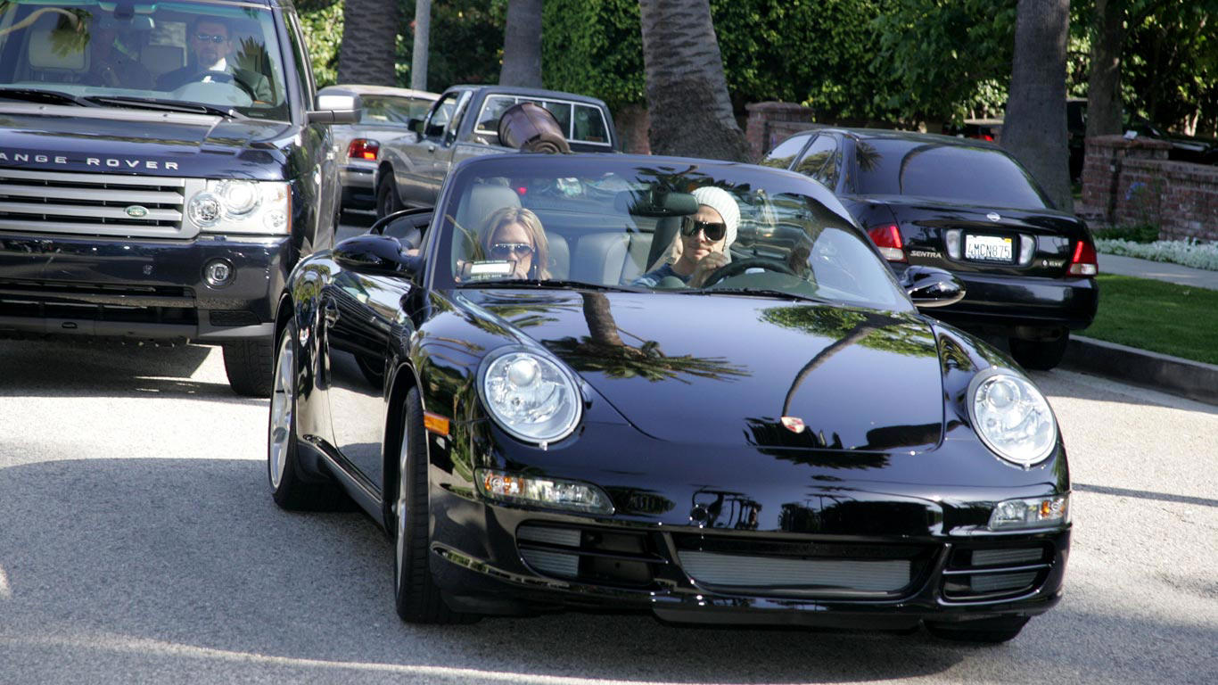 Slide 16 of 35: Followed by bodyguards, David Beckham gives wife Victoria a lift home in this Porsche 911 Cabriolet.