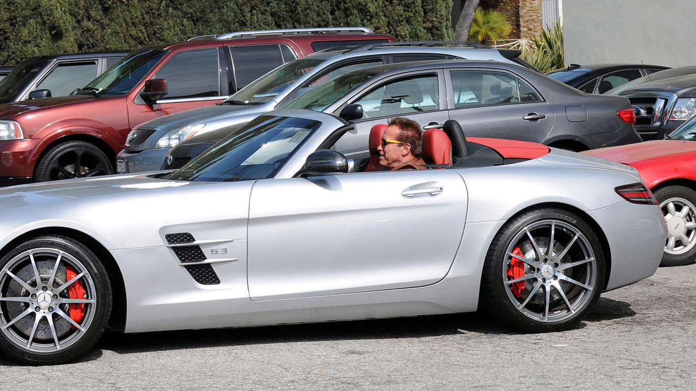 Slide 9 of 35: Arnie obviously likes his Mercs, too – as here he is again – this time in an SLS AMG Roadster.