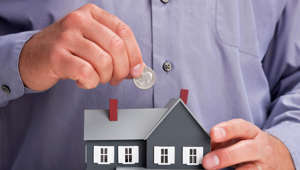 Close up of man holding coin and model house.