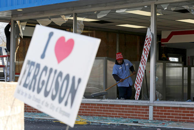 People clean up a business that was damaged in riots the previous night in Ferguson, Missouri, on November 25, 2014.