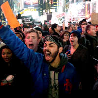 Protestors shout at Times Square after it was announced that the New York City police officer involved in the death of Eric Garner is not being indicted, Wednesday, Dec. 3, 2014, in New York. A grand jury cleared the white New York City police officer Wednesday in the videotaped chokehold death of Garner, an unarmed black man, who had been stopped on suspicion of selling loose, untaxed cigarettes, a lawyer for the victim's family said. A video shot by an onlooker and widely viewed on the Internet showed the 43-year-old Garner telling a group of police officers to leave him alone as they tried to arrest him. The city medical examiner ruled Garner's death a homicide and found that a chokehold contributed to it.