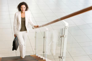 A young businesswoman is smiling and walking up office stairs and holding a briefcase.