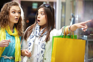 Surprised woman showing her friend things on sale in shopping mall