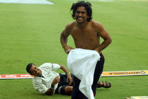 Indian cricketer Mahendra Singh Dhoni (R) runs back to the shelter of the dressing room after joking with teammate Sreesanth in the rain at the ground as the start of play was delayed by rain on the fourth day of the second test between India and West Indies at the Beausejour stadium in Gros Islet, St. Lucia 13 June 2006. West Indies put to follow-on by India are 43 runs for the loss of 1 wicket after play was called off due to rain.