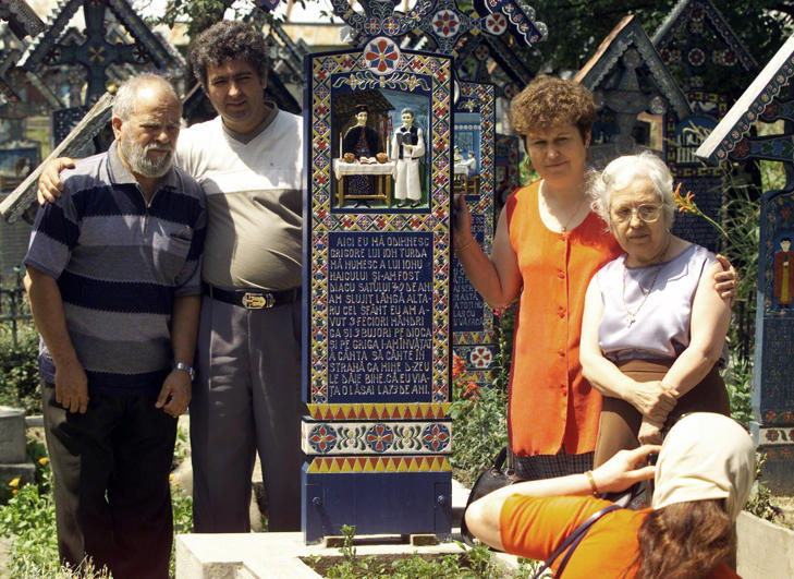 Tourists take a group picture around a painted cross in the Merry Cemetery of Sapanta, Romania.