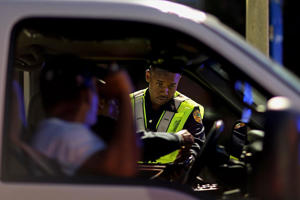 A Miami police officer speaks to a driver at a DUI checkpoint in Miami, Florida.