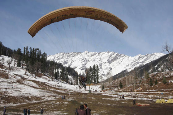 Slide 3 of 99: Tourists paraglide after fresh snowfall in Solang Nallah