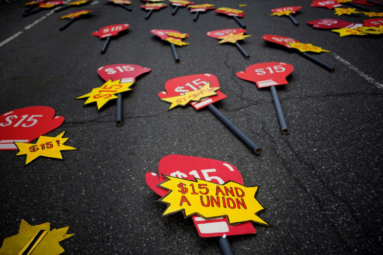 Signs lay in the street before the start of a rally in support of minimum wage increase in New York, U.S., on Wednesday, April 15, 2015.