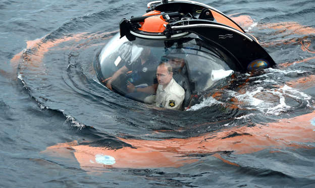 Slide 2 of 22: Russian President Vladimir Putin, centre, sits on board a bathyscaphe as it plunges into the Black sea along the coast of Sevastopol