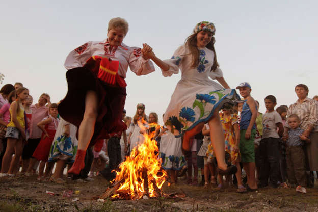 Διαφάνεια 3 από 12: Women jump over a campfire during the Ivan Kupala festival in the town of Turov, some 270 km (167 miles) south of Minsk, July 6, 2012. The traditional festival celebrates the summer solstice with overnight festivities such as people singing and dancing before jumping over campfires, as they believe it will purge them of their sins and make them healthier.