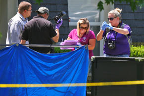 Investigators look down at a body behind a tarp, outside of a home in Broken Arrow, Okla., Thursday, July 23, 2015, where five family members were discovered stabbed to death. Two male teenagers are in custody. Police say they and the victims are related.