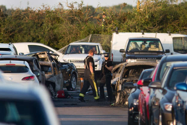 Emergency services inspect the crash site at Blackbushe Airport in Hampshire, after four people died when a private Phenom 300 jet crash-landed in a car auction site and burst into flames as it approached the runway in Farnborough, Britain, 31 July 2015. EPA