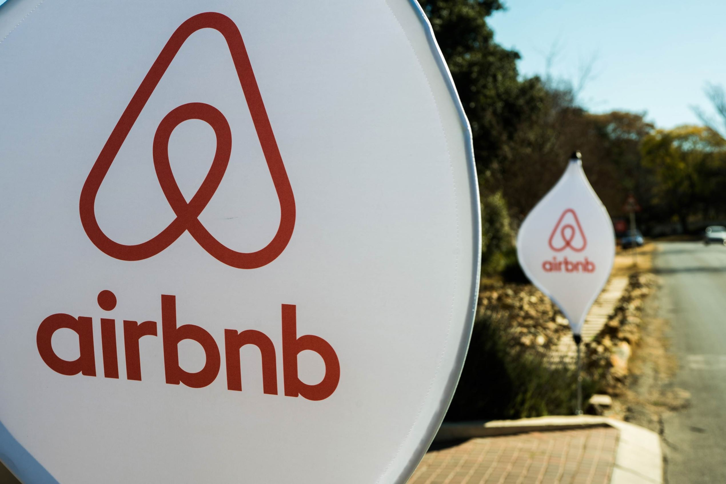 The logos of Airbnb Inc. on banners.