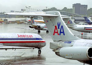 American Airlines passenger aircraft are seen at Lambert International Airport in St. Louis, Tuesday, Aug. 13, 2002.   AMR Corp., the parent of American Airlines, said Wednesday, Jan. 21, 2004,  it lost $111 million in the last three months of 2003 on modest gains in revenue and cost cutting.  The world's largest airline said the net loss was 70 cents per share, compared with a loss of $529 million, or $3.39 per share in the same period of 2002.  (AP Photo/James A. Finley)