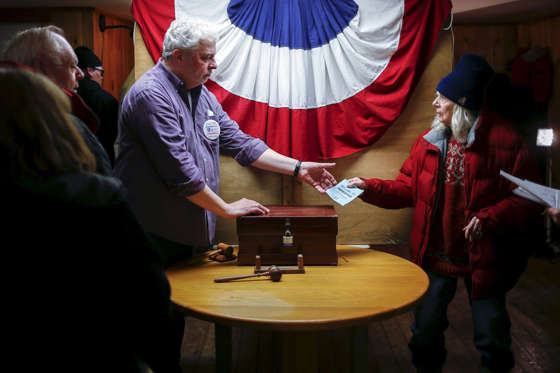Resident Nancy Holmes, 77, hands her ballot to town moderator Leslie Schoof as she votes in New Hampshire's first-in-the-nation primary at the town hall in Hart's Location, New Hampshire, February 9, 2016. The community of Hart's Location is one of three tiny New Hampshire towns that cast the state's first votes of the primary, as the clock strikes midnight.  Adrees Latif/Reuters