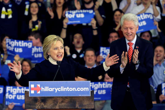 Democratic presidential candidate Hillary Clinton speaks as former President Bill Clinton applauds at her New Hampshire presidential primary campaign rally, Tuesday, Feb. 9, 2016, in Hooksett, N.H.