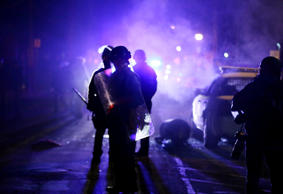 In this Nov. 25, 2014 file photo, police officers watch protesters as smoke fill...