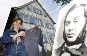 "Tanja Roppelt, manager of the Levi Strauss Museum presents a pair of jeans and a picture of inventor of the jeans, Levi Strauss, who was born in the house in Buttenheim, nearby Nuremberg, southern Germany, in this Sept. 22, 2002  photo.  Strauss died Sept. 26, 1902. Levi`s Jeans are worldfamous. Levi Strauss, the ""father"" of these blue trousers was born in Buttenheim in 1829 as Loeb Strauss. Levi Strauss emigrated to the United States in the year 1847. In San Francisco he founded his business dealing in textile clothing and all other things the gold-diggers and pioneers of the West needed. At first, jeans only made up part of the working garments of the people of the American West. But soon they became the most frequently worn pair of trousers in theworld. (AP Photo/Frank Boxler)"