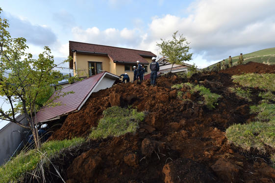 Slide 1 of 40: Policemen search for survivors at a landslide site after earthquakes in Minami-Aso, Kumamoto prefecture