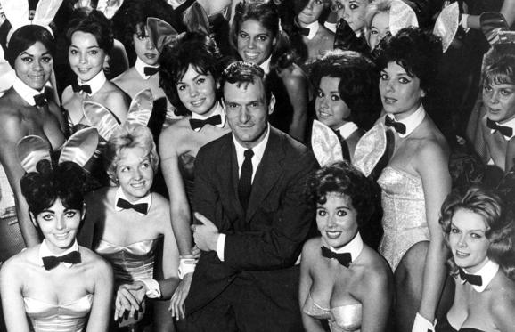 Slide 7 dari 28: Millionaire publisher of Playboy magazine Hugh Hefner poses with a bevy of bunny girls at one of America's chain of Playboy clubs. (Photo by Helmut Kretz/Getty Images)