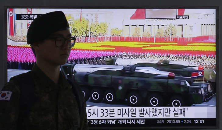 A South Korean army soldier passes by a TV news program showing a file footage of North Korean missiles on a military parade at Seoul Railway Station in Seoul, South Korea, Friday, April 15, 2016.