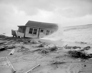This tiny cottage, named the F. Maroon, that was badly damaged by hurricane Connie, gets a new treatment from hurricane Diane in Wilmington Beach, N.C., on August 17, 1955. Damage from Diane is not expected to be as great as Connie. (AP Photo)