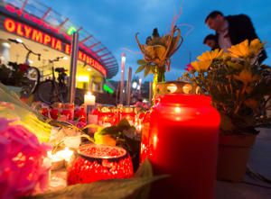 People gather to read tributes among the flowers and candles near to the Olympia shopping center where a shooting took place leaving nine people dead the day before in Munich, Germany, Saturday, July 23, 2016.