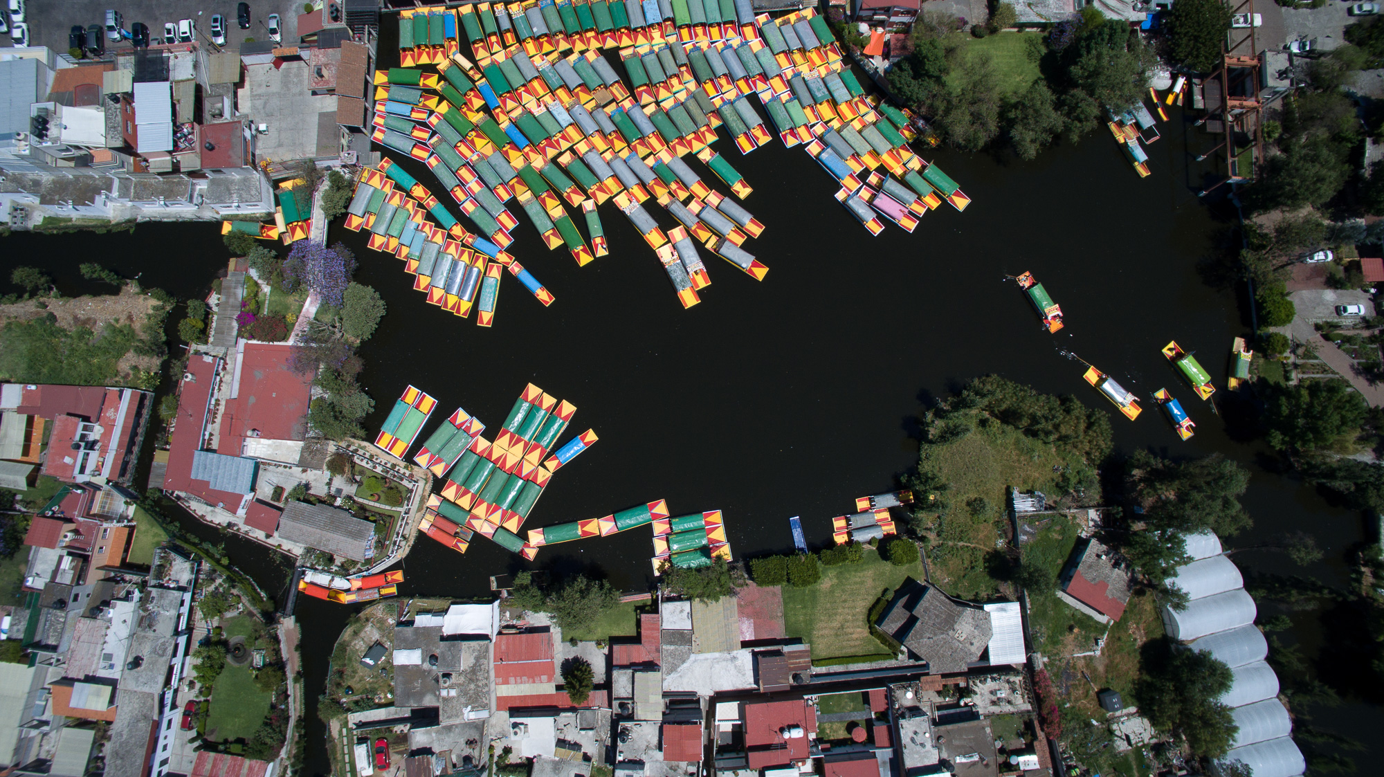 Slide 10 of 100: Aerial view taken with a drone of moored 'trajineras' -traditional flat-bottomed river boat- at Xochimilco natural reserve in Mexico City on April 1, 2016. Xochimilco canals are one of the places most visited by local and foreign tourists, to go along th