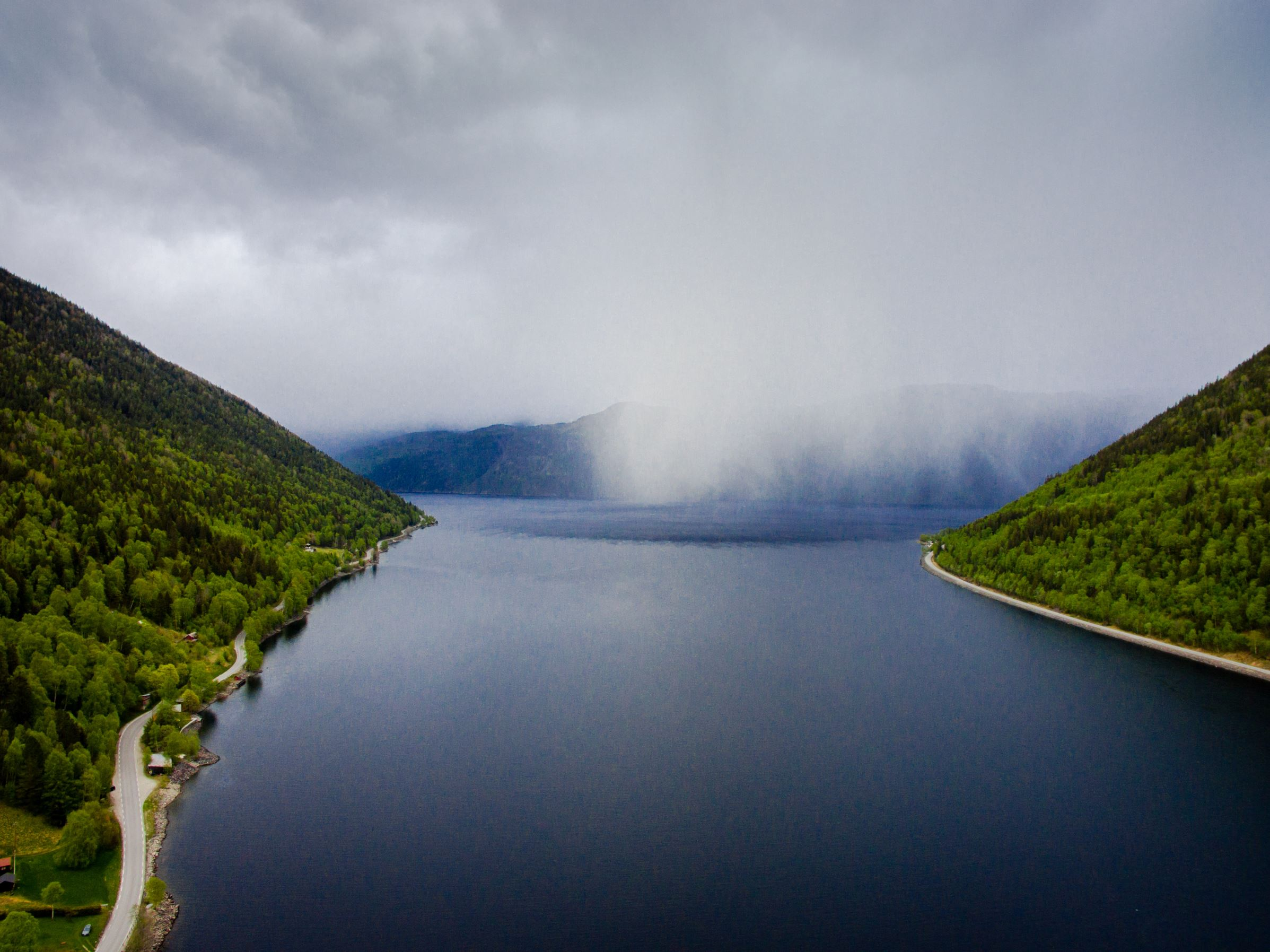 Slide 42 of 100: Part of the Lake Tinn in Rjukan, surrounded by mountains. The water is calm and the fog is falling over the lake. The photo was taken from a high angle view using a drone.  Lake Tinn is one of the largest lakes in Norway. It is situated between the munic