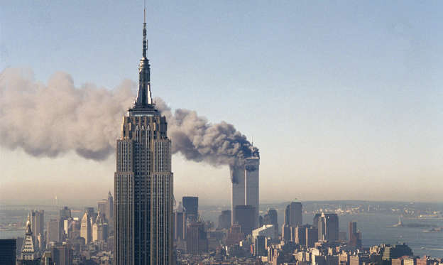 Slide 1 of 10: In this Sept. 11, 2001 file photo the twin towers of the World Trade Center burn behind the Empire State Building in New York after terrorists crashed two planes into the towers causing both to collapse.