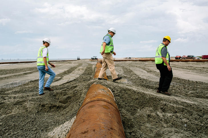 Members of the Louisiana Coastal Protection and Restoration Authority walk over pipeline on the beach at Port Fourchon, site of the Caminada Headland Beach and Dune Restoration project.