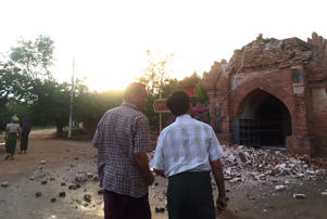 Two men look at a collapsed entrance of a pagoda after an earthquake in Bagan, Myanmar August 24, 2016.
