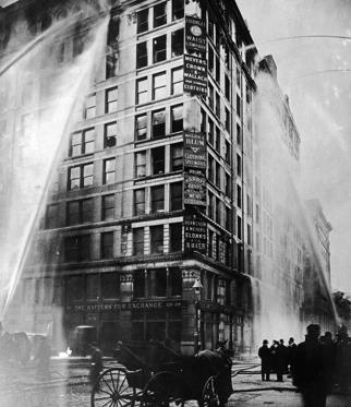Slide 1 of 12: Fire hoses spray water on the upper floors of the Asch Building (housing the Triangle Shirtwaist Company) on Washington and Greene Streets, during the fire in New York City, March 25, 1911.