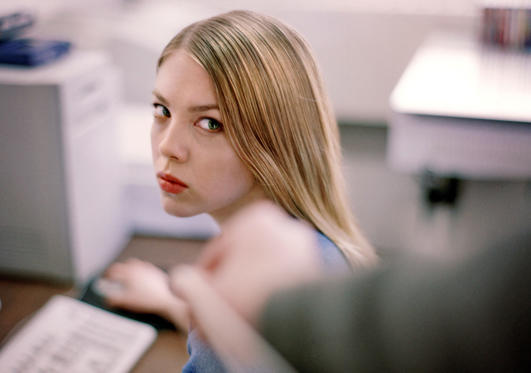 Slide 1 of 8: woman at desk giving dirty look to prankster