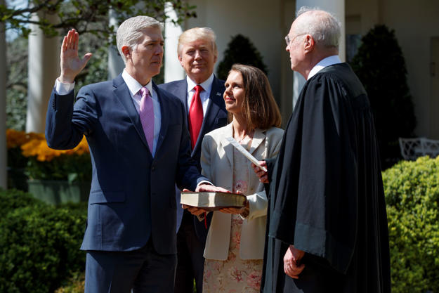 President Donald Trump watches as Supreme Court Justice Anthony Kennedy administers the judicial oath to Judge Neil Gorsuch during a re-enactment in the Rose Garden of the White House, Monday, April 10, 2017, in Washington. Gorsuch's wife Marie Louise hold a bible at center.