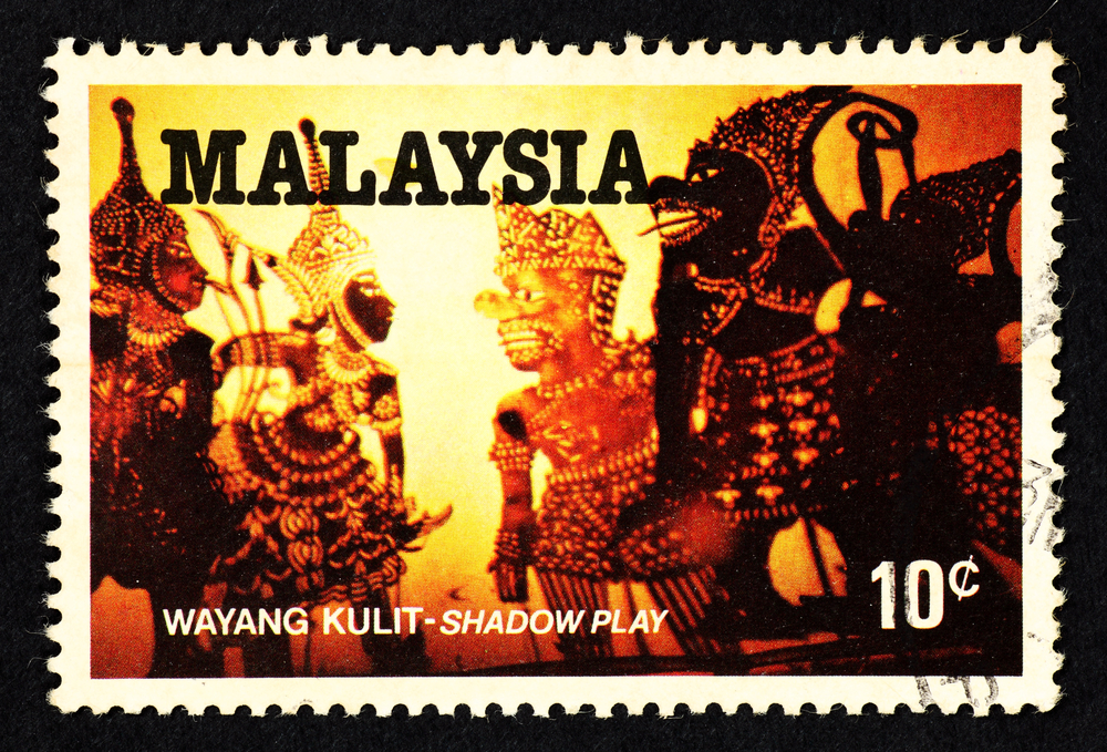 Slide 42 of 70: MALAYSIA - CIRCA 1982: Orange color postage stamp printed in Malaysia with image of he Malay traditional cultural puppet shadow play art known as Wayang Kulit.