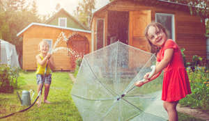 Happy children playing with garden sprinkler and umbrella in summer