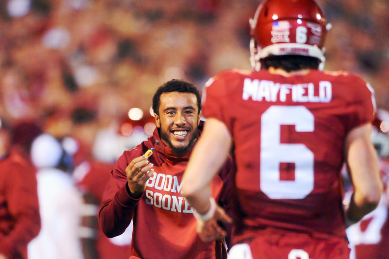 a man wearing a football uniform: Injured cornerback Zack Sanchez rewards quarterback Baker Mayfield #6 of the Oklahoma Sooners with a piece of gum after scoring a touchdown against the Iowa State Cyclones on Nov. 7, 2015 at Gaylord Family-Oklahoma Memorial Stadium in Norman, Oklahoma.