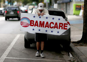 Pedro Rojas holds a sign directing people to an insurance company where they can sign up for the Affordable Care Act, also known as Obamacare, in 2015 in Miami, Florida.  Joe Raedle/Getty Images